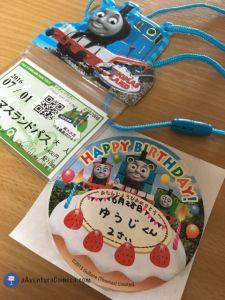 Esse cordão do Thomas de pescoço para colocar o ingresso é 600 ienes. E do lado o adesivo com nome do meu filho, idade e data de aniversário